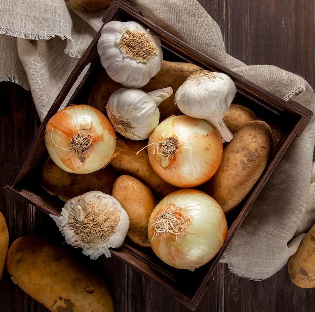 Vista dall'alto di aglio e cipolle in cassa