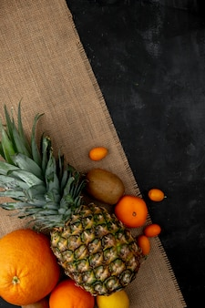 Vista dall'alto di agrumi come ananas arancione e altri su tela di sacco sulla superficie nera