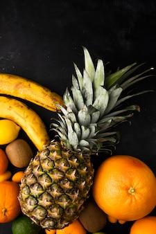 Vista dall'alto di agrumi come banana ananas arancione e altri sulla superficie nera