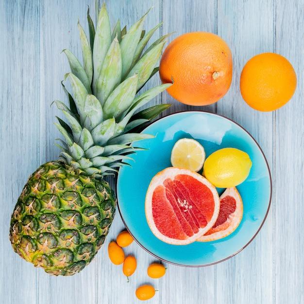 Vista dall'alto di agrumi come pompelmo e limone nel piatto con kumquat di mandarino arancio ananas su fondo in legno