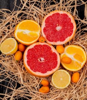 Vista dall'alto di agrumi come pompelmo limone e kumquat sulla superficie della paglia e sfondo nero