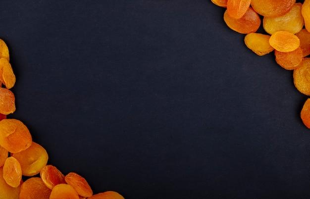 Vista dall'alto di albicocche secche su sfondo nero con spazio di copia