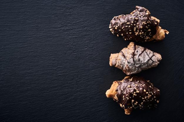 Vista dall'alto di alcune caramelle al cioccolato e torte su uno sfondo scuro.
