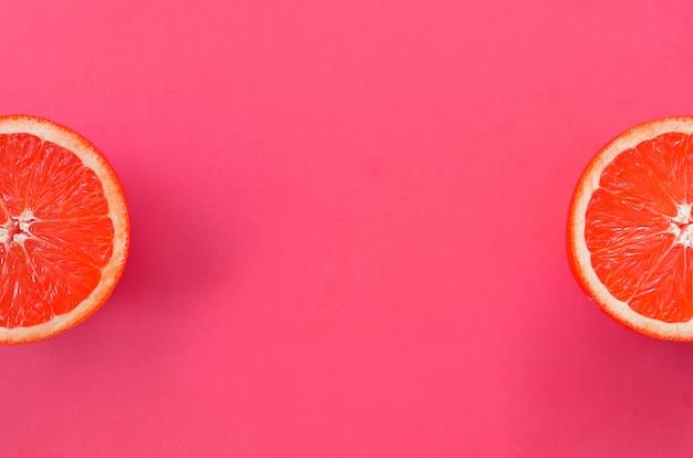 Vista dall'alto di alcune fette di pompelmo su sfondo luminoso in colore rosa.