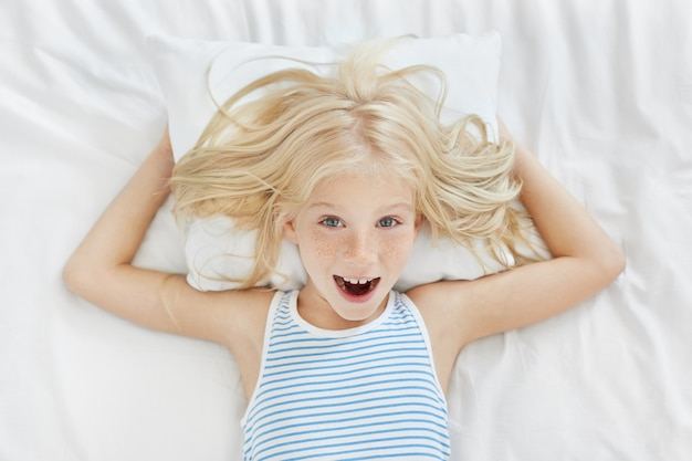 Vista dall'alto di allegra bambina con i capelli biondi, le lentiggini e gli occhi azzurri che indossa un pigiama spogliato sdraiato sul cuscino bianco e la biancheria nel suo letto, divertendosi e ridendo, non vuole fare un pisolino durante il giorno