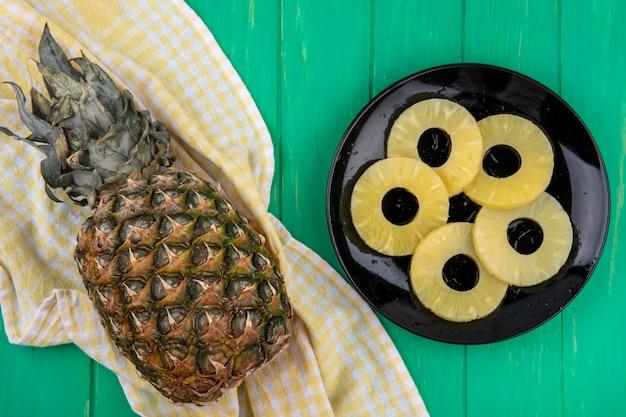Vista dall'alto di ananas sul panno plaid con fette di ananas nel piatto sulla superficie verde