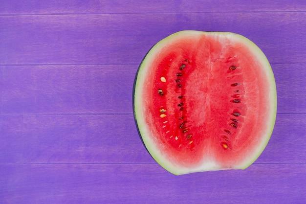 Vista dall'alto di anguria mezza a destra e sfondo viola con spazio di copia