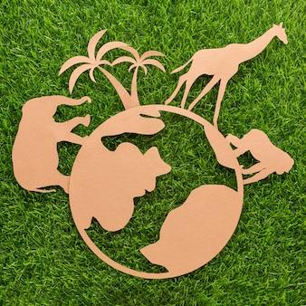 Vista dall'alto di animali di carta e pianeta sull'erba per la giornata degli animali