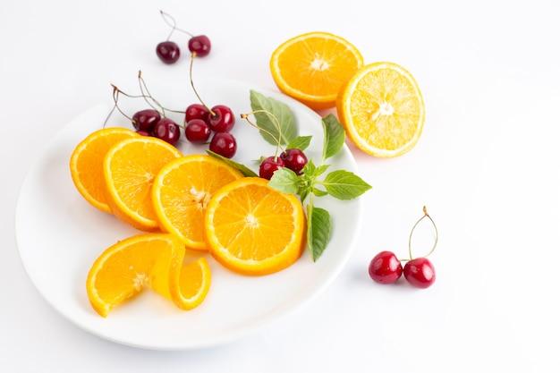 Vista dall'alto di arance fresche a fette all'interno del piatto bianco insieme a ciliegie rosse sul succo di colore della frutta esotica sfondo bianco