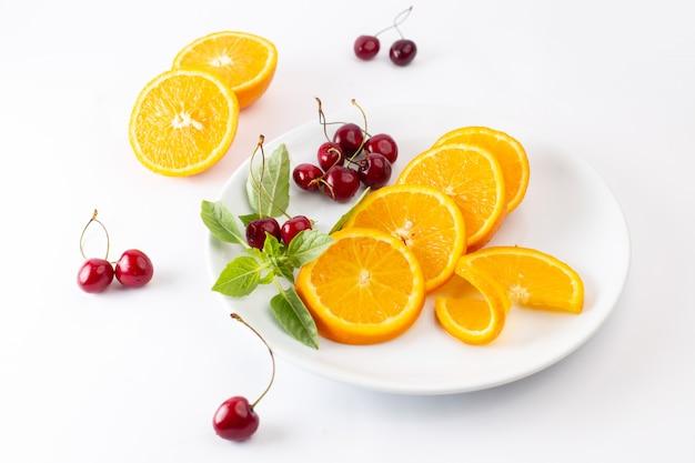 Vista dall'alto di arance fresche a fette all'interno del piatto bianco insieme a ciliegie rosse sul succo di colore della frutta esotica sfondo chiaro