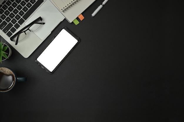 Vista dall'alto di articoli per ufficio con blocco note, laptop e tazza di caffè