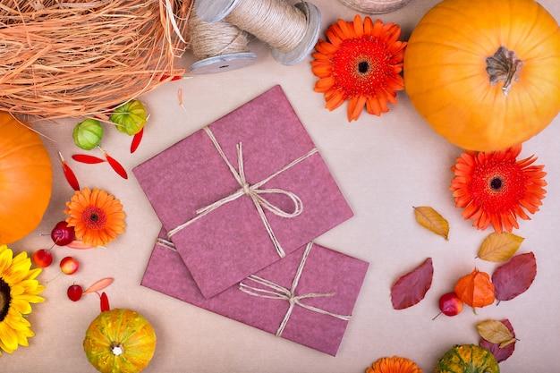 Vista dall'alto di artigianato confezione regalo, fiori gialli e arancioni e zucche su sfondo rosa. cartolina d'auguri in bianco per lavoro creativo. disteso