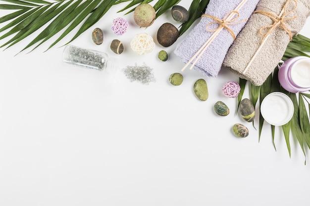 Vista dall'alto di asciugamani; crema idratante; pietre e foglie della stazione termale su superficie bianca