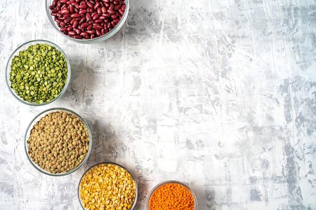 Vista dall'alto di assortimento di piselli, lenticchie, fagioli e legumi su sfondo bianco.
