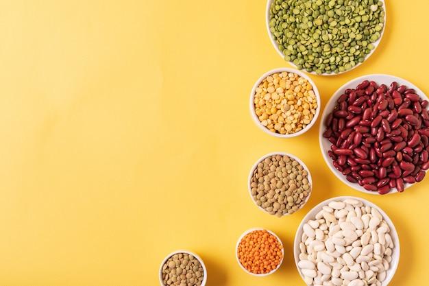 Vista dall'alto di assortimento di piselli, lenticchie, fagioli e legumi su sfondo giallo.
