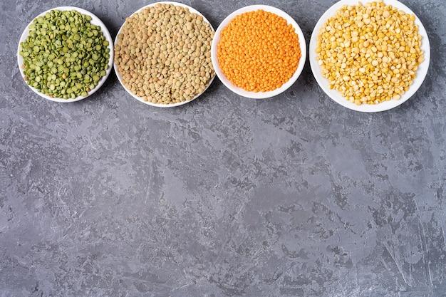 Vista dall'alto di assortimento di piselli, lenticchie, fagioli e legumi su sfondo grigio.