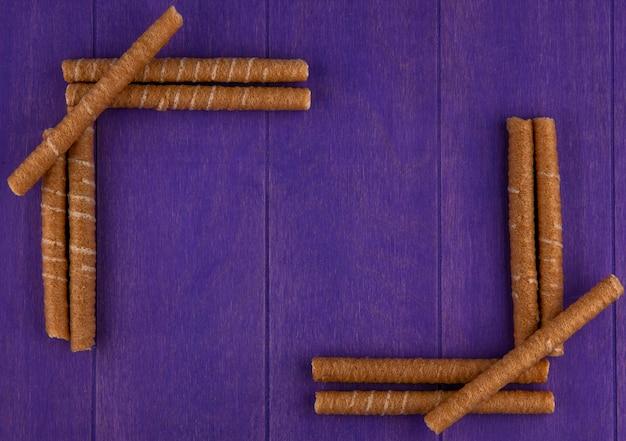 Vista dall'alto di bastoncini croccanti su sfondo viola con spazio di copia