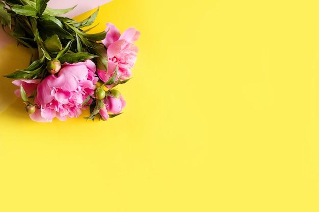 Vista dall'alto di belle peonie rosa sul muro giallo, copia spazio