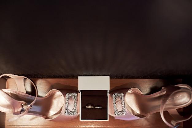 Vista dall'alto di bellissimi sandali rosa e anelli di nozze d'oro con diamanti
