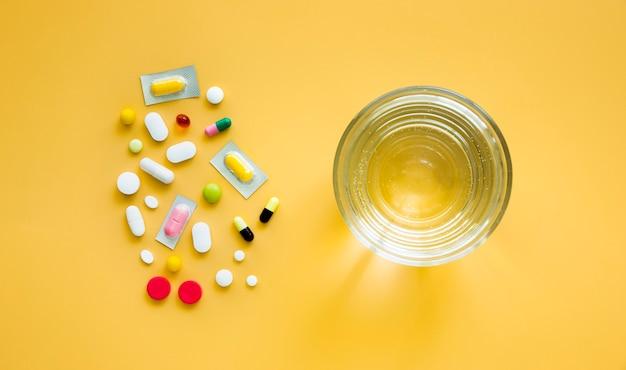 Vista dall'alto di bicchiere d'acqua e pillole multiple