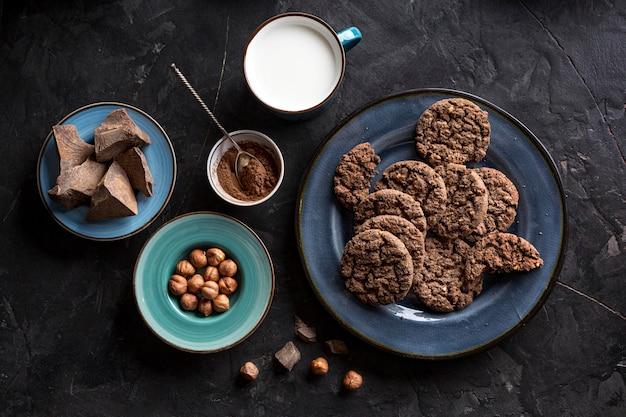 Vista dall'alto di biscotti al cioccolato sul piatto con latte e nocciole