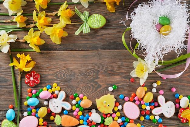 Vista dall'alto di biscotti, caramelle e fiori di pasqua