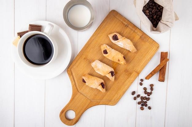 Vista dall'alto di biscotti di farina con marmellata di fragole su una tavola di legno con una tazza di caffè su sfondo bianco