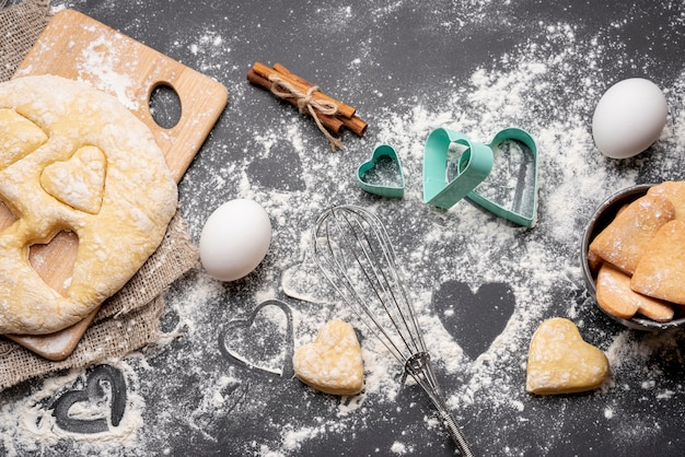 Vista dall'alto di biscotti di san valentino con utensili da cucina