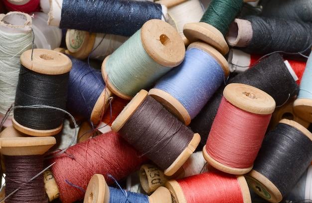 Vista dall'alto di bobine di filati multicolore di molti pantaloni a vita bassa vintage. atelier, accessori per cucire