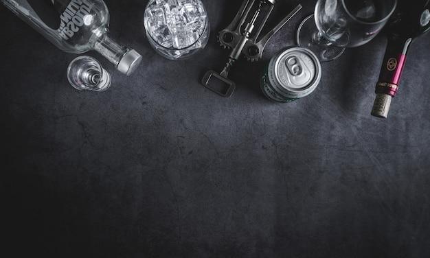 Vista dall'alto di bottiglia di vino, bottiglia di vodka, cubetto di ghiaccio, birra e cavatappi
