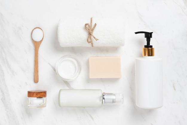 Vista dall'alto di bottiglie cosmetiche, sapone, cucchiaio di legno e asciugamano su marmo bianco.