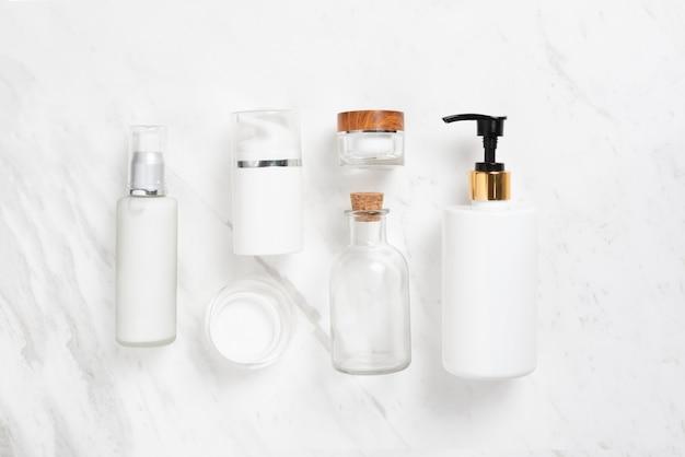 Vista dall'alto di bottiglie cosmetiche su marmo bianco.