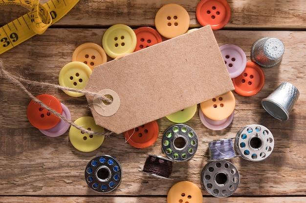 Vista dall'alto di bottoni con tag e navette per macchine da cucire