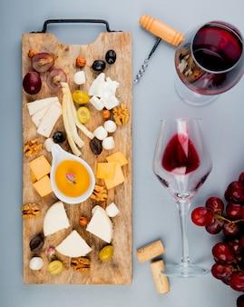 Vista dall'alto di burro con diversi tipi di formaggio uva olive noci sul tagliere e bicchieri di vino con tappi e cavatappi su bianco