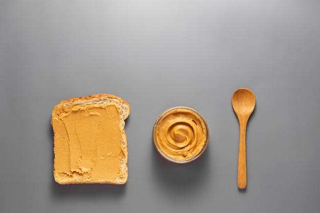 Vista dall'alto di burro di arachidi e pane tostato di arachidi su sfondo grigio.