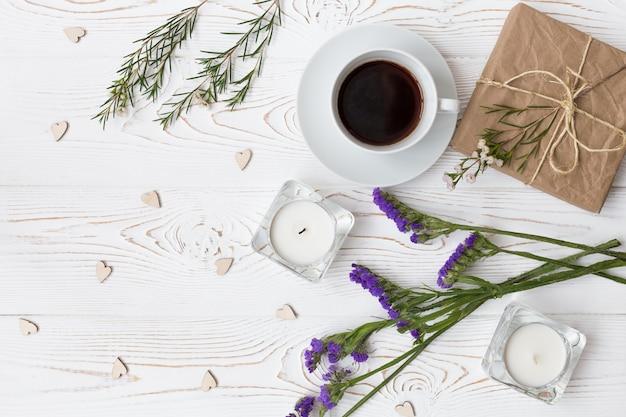 Vista dall'alto di caffè, regali, cuori, candele, fiori su legno bianco