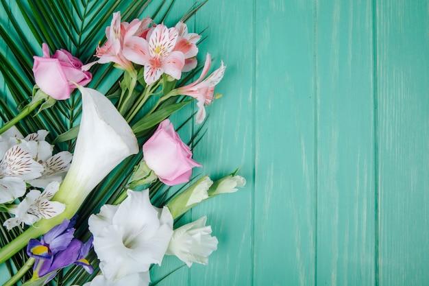 Vista dall'alto di calle e gladioli di colore bianco con iris viola scuro e rose rosa e fiori di alstroemeria su foglia di palma su fondo di legno verde con spazio di copia