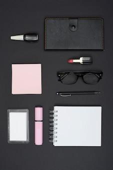 Vista dall'alto di cancelleria per ufficio e rossetto; smalto per unghie su sfondo nero