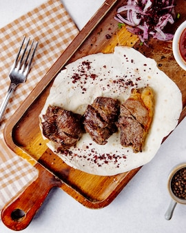 Vista dall'alto di carne arrosto con cipolle rosse su una tavola di legno