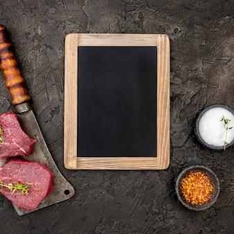 Vista dall'alto di carne con mannaia e lavagna