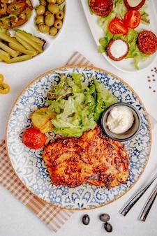 Vista dall'alto di carne di pollo al forno con formaggio grigliato di patate e pomodori