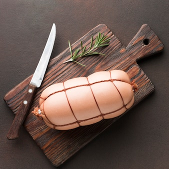 Vista dall'alto di carne fresca con coltello e rosmarino