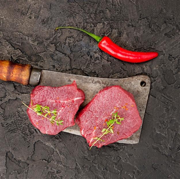 Vista dall'alto di carne su mannaia con erbe e peperoncino