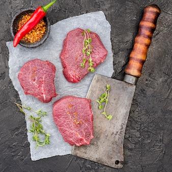 Vista dall'alto di carne su mannaia con spezie e peperoncino