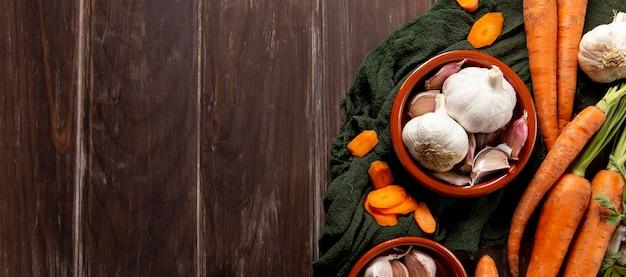 Vista dall'alto di carote e ciotola di aglio