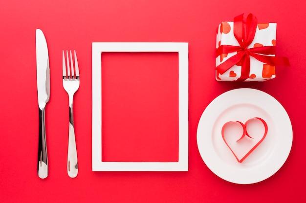 Vista dall'alto di carta a forma di cuore sul piatto con cornice e posate