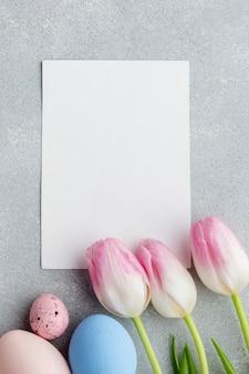 Vista dall'alto di carta bianca con tulipani e uova colorate di pasqua