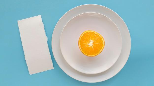 Vista dall'alto di carta menu vuoto con piatti e arancio