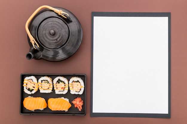 Vista dall'alto di carta menu vuoto con teiera e sushi