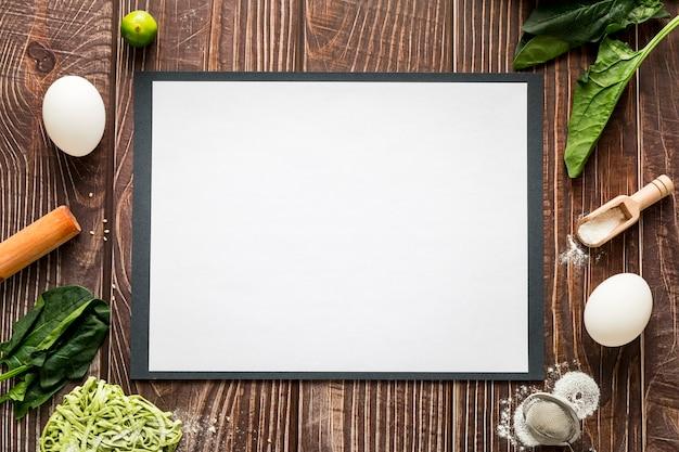Vista dall'alto di carta menu vuoto con uova e verde